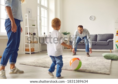 Happy family staying at home, having fun together and engaging their small child in sport games. Young dad with little son playing football with inflatable ball in living-room Royalty-Free Stock Photo #1831389634