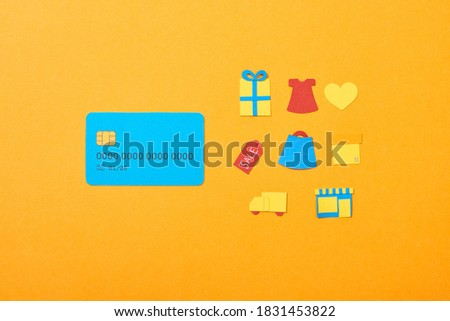flat lay with blue credit card template near shopping icons isolated on orange,stock image