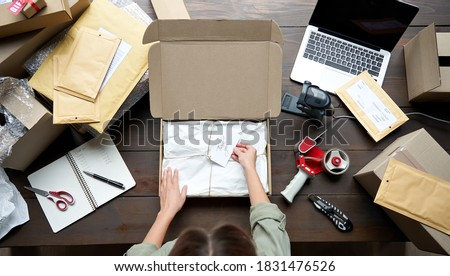 Top above closeup view of female online store small business owner entrepreneur packing package post shipping box preparing delivery parcel on table. Ecommerce dropshipping shipment service concept. #1831476526