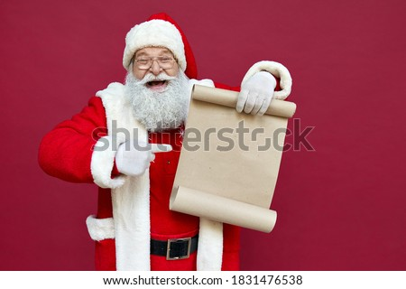 Happy excited old bearded Santa Claus wearing costume holding Merry Christmas wishlist paper roll pointing finger at blank empty xmas wish list letter standing isolated on red background, copy space. #1831476538
