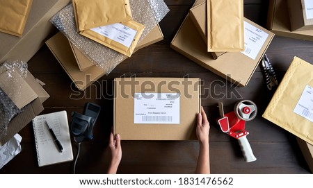 Above table top view of female warehouse worker or seller packing ecommerce shipping order box for dispatching, preparing post courier delivery package, dropshipping shipment service concept. Royalty-Free Stock Photo #1831476562