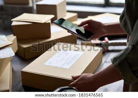 Female warehouse worker seller, small stock business owner holding phone scanning retail package parcel bar code on commercial shipping box delivery order on smartphone using mobile app. #1831476565