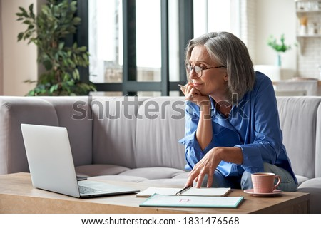 Senior mature older woman watching business training, online webinar on laptop computer remote working or social distance learning from home. 60s businesswoman video conference calling in virtual chat Royalty-Free Stock Photo #1831476568