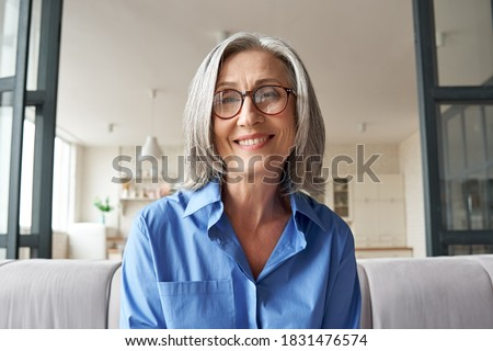 Smiling mature 60s middle aged woman looking at web camera video conference calling in virtual web chat remote business meeting by social distance remote videocall. Headshot face portrait. Webcam view #1831476574