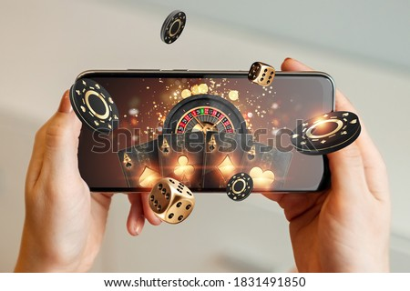 Creative background, online casino, in a man's hand a smartphone with playing cards, roulette and chips, black-gold background. Internet gambling concept. Copy space.