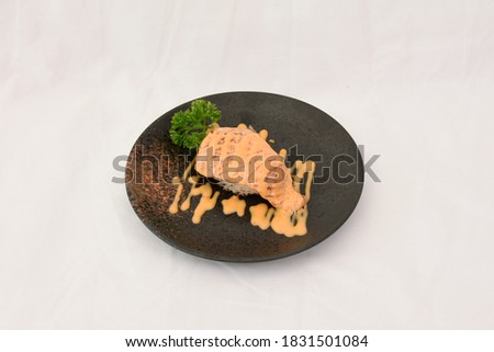Burnt salmon sushi with mayo sauce served on black plate, isolated in white backgroud. Simply use for Japanese restaurant as picture menu