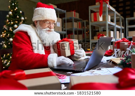 Happy old Santa Claus wearing costume holding gift box using laptop computer sitting at workshop table on Merry Christmas eve. Ecommerce website xmas time holiday online shopping sale concept. #1831521580