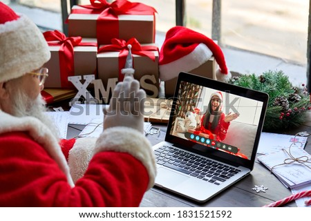Over shoulder view of Santa Claus video calling kid girl on laptop greeting child by webcam talk open Christmas gift box in virtual online chat meeting using computer sit at workshop table on xmas. #1831521592