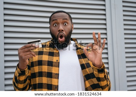 Excited African American man holding credit card for online shopping, showing ok sign