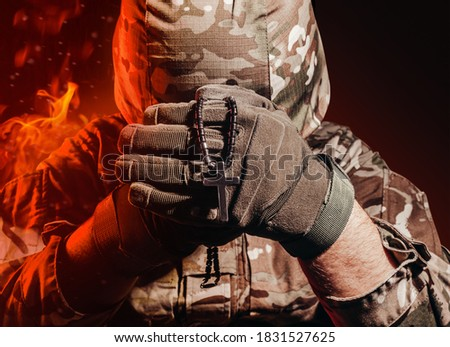 Photo of a military soldier in uniform and armor helmet sitting and holding cross religious necklace on back background with red fire burning glow. Royalty-Free Stock Photo #1831527625