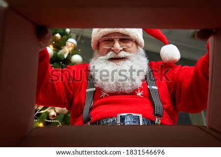 Happy old bearded Santa Claus wearing hat packing present looking inside cardboard box wrapping gift preparing package delivery on xmas eve. Merry Christmas surprise concept, close up view from below.