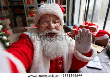 Happy old bearded Santa Claus wearing costume holding phone waving hand taking selfie, video calling, recording video Merry Christmas greeting or shooting vlog standing in workshop, face camera view. #1831546699