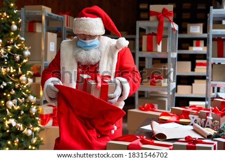 Old funny bearded Santa Claus wearing costume, face mask, packing presents gift boxes in sack bag preparing for xmas eve in workshop. Merry Christmas Covid 19 coronavirus safe delivery concept. #1831546702