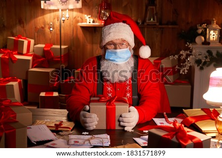 Old funny bearded Santa Claus wearing face mask, holding gift box preparing for xmas eve sitting at cozy home table late in night with presents. Merry Christmas Covid 19 coronavirus safe delivery. #1831571899