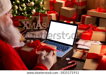 Over shoulder view of Santa Claus holding xmas gift using laptop computer with white blank empty mock up screen monitor for e commerce website ad sitting at decorated table on Merry Christmas eve. #1831571911