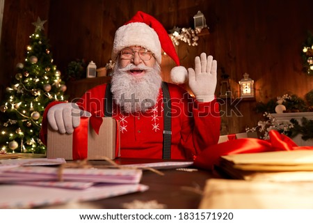 Happy Santa Claus, Saint Nicholas holding letter looking to camera, talking to webcam video calling or recording Happy New Year, Merry Christmas greetings on xmas eve sitting at table late at home. #1831571920