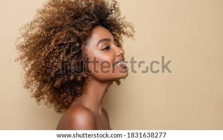 Beauty portrait of african american girl with clean healthy skin on beige background. Smiling dreamy beautiful black woman.Curly  hair in afro style  Royalty-Free Stock Photo #1831638277