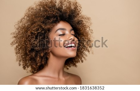 Beauty portrait of african american girl with clean healthy skin on beige background. Smiling dreamy beautiful black woman.Curly  hair in afro style  Royalty-Free Stock Photo #1831638352