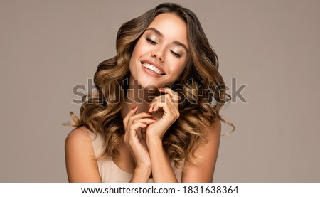 Beautiful smiling woman holding hands near face. Beauty girl  with curly hair   . Presenting your product. Expressive facial expressions . Wavy hairstyle Royalty-Free Stock Photo #1831638364