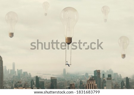 surreal moment of a woman traveling on a swing carried by a light bulb over a metropolis Royalty-Free Stock Photo #1831683799