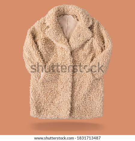 women's yellow fur coat made of faux fur, as if levitating, on a pink background, sleeves tucked into pockets, concept #1831713487