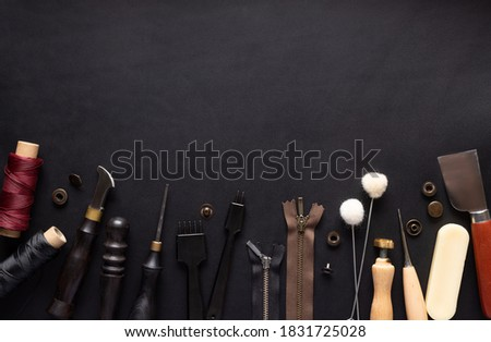 border of various tools for sewing leather goods. Handmade wallets, belts, bags. Composition on black leather background with free space for text or design. Top view Royalty-Free Stock Photo #1831725028