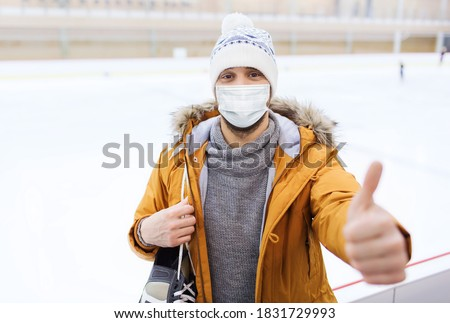 people, sport, gesture and leisure concept - young man wearing face protective medical mask for protection from virus disease with ice-skates showing thumbs up on skating rink