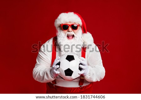 Portrait of his he attractive cheerful cheery ecstatic fat white-haired Santa holding in hands soccer ball having fun isolated bright vivid shine vibrant red burgundy maroon color background #1831744606
