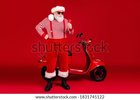 Full length body size view of his he handsome focused bearded Santa father riding moped using gadget chatting blogging post comment feedback isolated bright vivid shine vibrant red color background