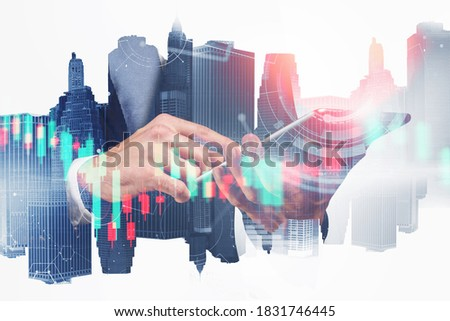 Hand of businessman using tablet in blurry city with double exposure of financial charts. Toend image