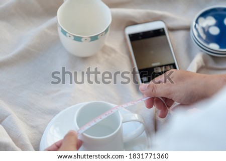 Selective focus a tape measure, Young women taking pictures of glass, ceramics. To prepare to sell on the online market It is a good business that can generate good income. Home studio background