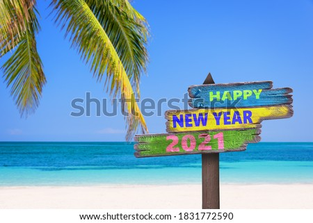 Hapy new year 2021 on a colored wooden direction signs, beach and palm tree background
