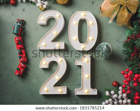 New year festive green background with 2021 illuminated numbers with ornament and toy train and tree decor on dark green. #1831785214