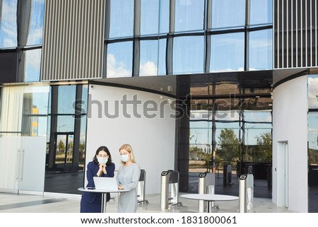 Wide angle portrait of two successful businesswomen wearing masks while looking at laptop screen standing at desk in office building, copy space Royalty-Free Stock Photo #1831800061