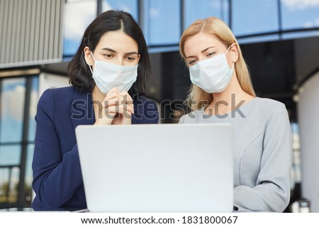 Waist up portrait of two successful businesswomen wearing masks while looking at laptop screen standing at desk in office building Royalty-Free Stock Photo #1831800067