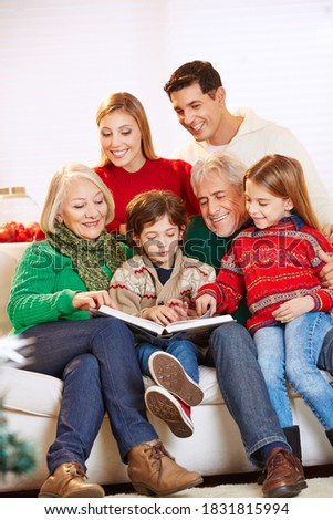 Happy family with grandparents reading a book at Christmas