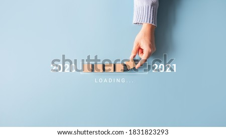 Loading new year 2020 to 2021 with hand putting wood cube in progress bar. Royalty-Free Stock Photo #1831823293