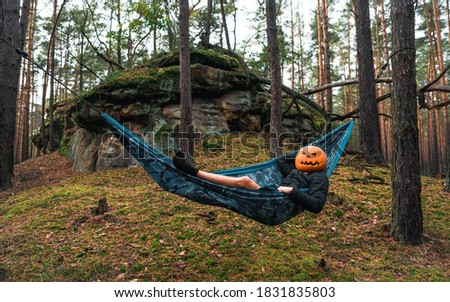 Halloween Scarecrow with a carved pumpkin in relax in Hammocks on trees in the forest it seems they are planning something indecent. Gloomy forest. An ideal image for fall, halloween.