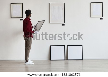 Full length portrait of African-American man planning art gallery or exhibition while setting up frames on white wall, copy space