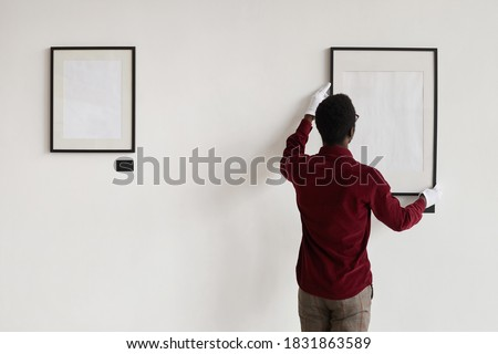 Back view at African-American man hanging blank frames on wall while planning art gallery or exhibition, copy space