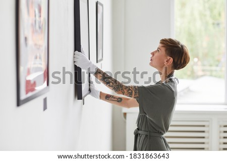 Side view portrait of tattooed creative woman hanging paintings on wall while planning art gallery exhibition, copy space Royalty-Free Stock Photo #1831863643