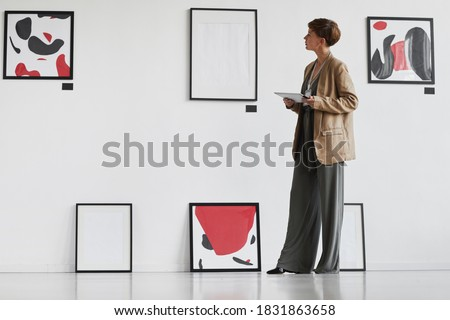 Full length portrait of creative elegant woman looking at paintings hanging on white wall while visiting modern art gallery exhibition, copy space Royalty-Free Stock Photo #1831863658