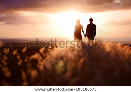 Young couple enjoying the sunset in the meadow #183188573