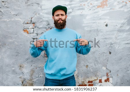City portrait of handsome hipster guy with beard wearing blue blank sweatshirt with space for your logo or design. Mockup for print