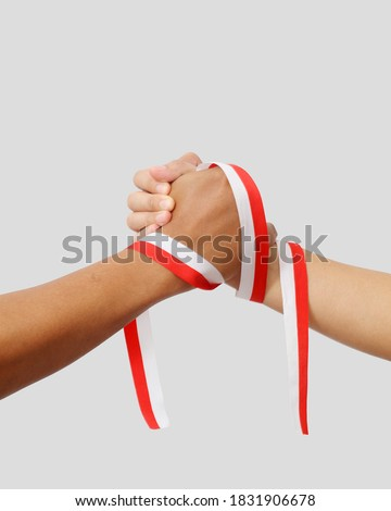 The hands of a man holding a red and white ribbon as a symbol of the Indonesian flag. Isolated on gray background