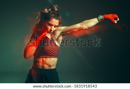 Close portrait of a female mixed martial arts fighter with a bandage on her hands. Long exposure shot Royalty-Free Stock Photo #1831918543