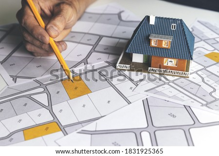 choose a building plot of land for house construction on cadastral map Royalty-Free Stock Photo #1831925365