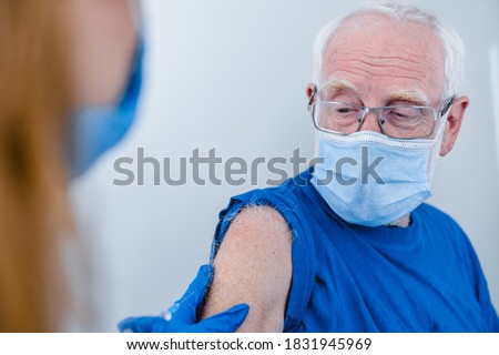 Close up photo of senior man`s arm with doctor`s hands making injection. Elderly patient wearing mask to stop coronavirus spread Royalty-Free Stock Photo #1831945969