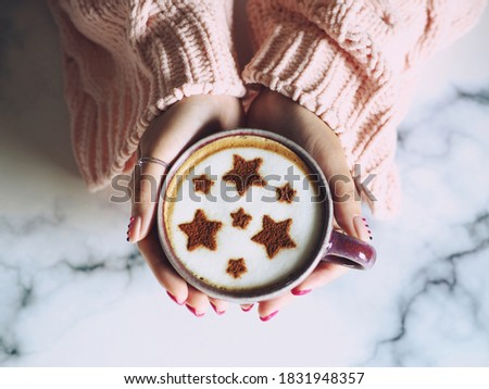 Coffee cup with star symbols on frothy surface served in coffee cup holding by female hands with acrylic paint nail polish. Holidays food art theme for special moments. (top view, selective focus)