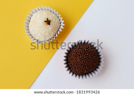 Coconut Candy and Brigadier's sweet (Beijinho and Brigadeiro, in portuguese) on yellow and white background. Brazilian Handmade candies.  Royalty-Free Stock Photo #1831993426